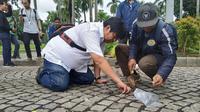 Petugas memperhatikan bekas aspal di Monas. (Merdeka.com/Yunita Amalia)