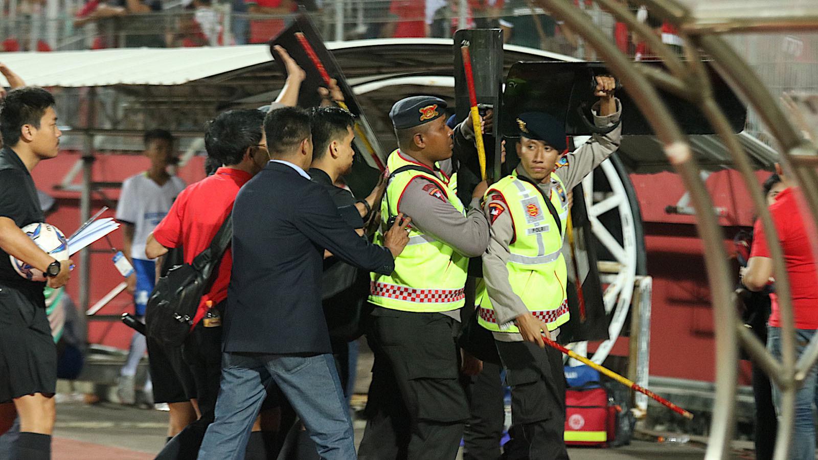 Wasit saat duel Malaysia vs Indonesia di semifinal Piala AFF U-19 2018 (12/7/2018) di Stadion Gelora Delta, Sidoarjo, mendapat perlindungan dari aparat keamanan. (Bola.com/Aditya Wany)