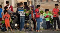 Sejumlah anak saat menjual sayur-sayuran dan buah-buahan untuk membantu keluarga mereka menghasilkan sedikit uang selama bulan suci Ramadhan di Gaza (19/5/2019). (AP Photo/Hatem Moussa)