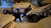 Seorang pria terjatuh saat mendorong mobil yang terjebak salju tebal di Madrid, Spanyol, Jumat (8/1/2021). Badai Filomena mengakibatkan salju lebat turun di Madrid dan sebagian besar wilayah Spanyol. (OSCAR DEL POZO/AFP)