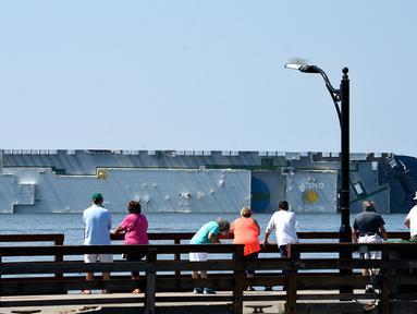 Warga melihat kapal kargo Golden Ray yang terbalik di lepas pantai negara bagian Georgia, Amerika Serikat, Minggu (8/9/2019). Kapal kargo Korea Selatan yang mengangkut 4.000 mobil itu terbalik saat menuju Timur Tengah. (Bobby Haven/The Brunswick News via AP)