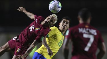 Bek Venezuela, Roberto Rosales menyundul bola saat bersaing dengan penyerang Brasil, Roberto Firmino dalam laga Kualifikasi Piala Dunia 2022 Zona Amerika Selatan, di Estadio Morumbi, Sao Paulo, Brazil, Jumat (13/11/2020). Brasil berhasil mengalahkan Venezuela 1-0. (Fernando Bizerra/Pool via AP)