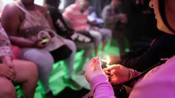 Seorang wisatawan wanita mengisap ganja di dalam bus Green Line Trips di Los Angeles, Amerika Serikat, Sabtu (19/5). Industri ganja California menargetkan wisatawan serta penduduk setempat, tur, toko, penginapan, dan iklan. (AP Photo/Richard Vogel)