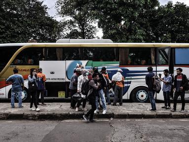 Suasana penumpang bus antarkota antarprovinsi (AKAP) saat tiba di Terminal Kampung Rambutan, Jakarta, Minggu (3/1/2021). Berdasarkan data Dishub Terminal Kampung Rambutan per tanggal 2 Januari 2021 jumlah penumpang bus yang tiba di Jakarta sebanyak 34.220 penumpang. (merdeka.com/Iqbal S. Nugroho)