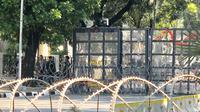 Penjagaan jalan menuju Mahkamah Konstitusi (MK) diperketat. Personel polisi serta TNI terlihat sudah berjaga di belakang pagar pembatas polisi dan kawat berduri yang terletak depan Kementerian Pertahan (Kemenhan) RI. (Liputan6/Ratu Annisa)