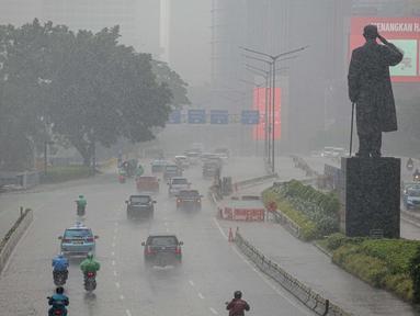 Sejumlah kendaraan melintas di tengah hujan lebat di kawasan Jalan Sudirman, Jakarta, Selasa (29/6/2021). BMKG mengungkapkan wilayah Jakarta dan sekitarnya masih dilanda hujan dan hawa dingin di musim kemarau. (Liputan6.com/Faizal Fanani)