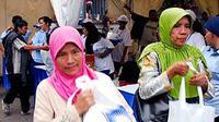 Dua perempuan membawa bingkisan sembako gratis yang dibagikan dalam rangka HUT ke-12 PAN (Partai Amanat Nasional) di Parkir Selatan Senayan, Jakarta.(Antara)
