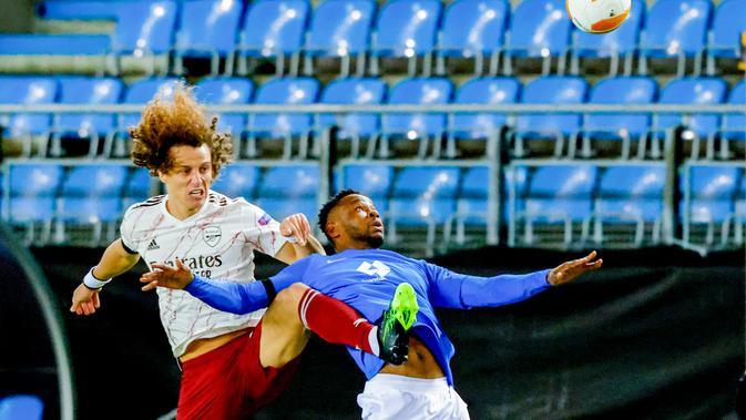 Bek Arsenal, David Luiz berebut bola dengan pemain Molde, Leke James pada pertandingan Grup B Liga Europa di Stadion Aker di Molde, Norwegia, Kamis (26/11/2020). Arsenal menang telak 3-0 atas Molde. (Svein Ove Ekornesvag / NTB via AP)