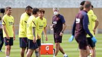 Pelatih Barcelona, Quique Setien, mengamati anak asuhnya saat menggelar latihan di Joan Gamper, Barcelona, Senin (25/5/2020). Latihan tersebut untuk persiapan jelang kembali bergulirnya La Liga Spanyol. (AFP/Miguel Rui)
