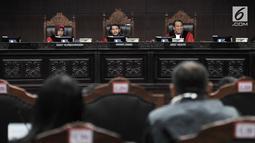 Ketua Hakim MK Anwar Usman (tengah) bersama Hakim MK Enny Nurbaningsih (kiri) dan Arie Hidayat memimpin sidang perdana sengketa Pemilu Legislatif 2019 di Gedung MK, Jakarta, Selasa (9/7/2019). Ada 260 perkara gugatan dari peserta Pileg 2019 yang akan disidangkan. (merdeka.com/Iqbal Nugroho)