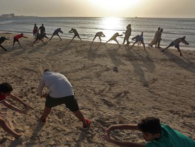 Orang-orang berolahraga di pantai sembari menunggu waktu berbuka puasa selama bulan suci Ramadan, meskipun lockdown karena pandemi COVID-19, di ibu kota Tripoli, Libya pada Jumat (8/5/2020). (Photo by Mahmud TURKIA / AFP)