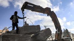Seorang pekerja Palestina berdiri di samping balok-balok beton rusak yang ditarik oleh derek sebagai bagian dari penyelamatan bahan konstruksi bangunan yang hancur selama konflik Mei 2021 antara Hamas dan Israel di Kota Gaza, Sabtu (5/6/2021). (MAHMUD HAMS/AFP)
