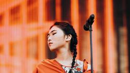 Penyanyi kelahiran tahun 1993 ini tampil dengan penuh penghayatan. Masih ditemani keyboard kesayangannya, dengan pakaian berwarna putih bercorak bunga-bunga dan outer berwarna oranye, ia tampak menawan dengan rambut dikepang (Liputan6.com/IG/@isyanasarasvati)