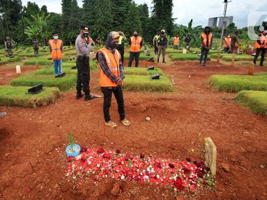 Sejumlah pelanggar PSBB berdoa di makam korban Covid-19 di TPU Jombang, Tangerang Selatan, Senin (18/1/2020). Petugas Satpol PP bersama Polres Tangsel memberikan hukuman bagi 17 pelanggar PSBB yang terkena razia masker di kawasan Bintaro. (merdeka.com/Arie Basuki)