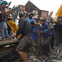 Tim penyelamat membantu korban yang ditarik keluar dari reruntuhan gedung pemerintah yang runtuh saat gempa bumi di Mamuju, Sulawesi Barat, Jumat (15/1/2021). Gempa bermagnitudo 6,2 mengguncang Mamuju, Sulawesi Barat. (AP Photo/Azhari Surahman)