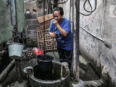 Warga menggunakan sumur timba untuk keperluan mandi, cuci, dan kakus (MCK) di kawasan Sukapura, Cilincing, Jakarta, Senin (22/3/2021). Sumur timba masih menjadi sumber air utama bagi sebagian warga di RW 005 Kelurahan Sukapura. (merdeka.com/Iqbal S. Nugroho)