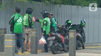 Driver ojek online berbincang di kawasan Jakarta, Jumat (10/4/2020). Peraturan Gubernur DKI Jakarta dalam pelaksanaan PSBB mengatur angkutan roda dua seperti ojek online maupun ojek konvensional dilarang membawa penumpang.  (Liputan6.com/Herman Zakharia)