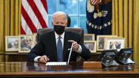 Presiden Amerika Serikat Joe Biden setelah menandatangani Perintah Eksekutif yang membatalkan larangan bagi transgender untuk masuk militer AS pada era Donald Trump di Kantor Oval Gedung Putih, Washington, Senin (25/1/2021). (AP Photo/Evan Vucci)