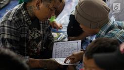 Anak punk saat belajar mengaji di kolong flyover Tebet, Jakarta, Sabtu (8/12). Dengan konsep persahabatan, komunitas ini mengajak anak-anak punk dan anak jalanan menyiapkan diri untuk kembali masuk ke dalam masyarakat. (Merdeka.com/Imam Buhori)