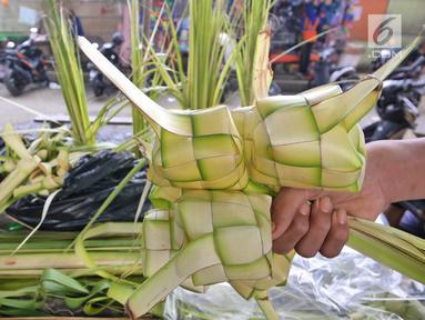 Pedagang menunjukkan satu ikat kulit ketupat siap jual di Pasar Kemiri Muka, Depok, Jawa Barat, Selasa (12/6). Menjelang Lebaran, pedagang kulit ketupat mengaku kebanjiran pembeli. (Liputan6.com/Herman Zakharia)