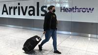 Potret yang diambil pada 10 Juli 2020 ini, menampilkan penumpang mengenakan masker akibat pandemi COVID-19, baru tiba di Bandara Heathrow, London barat. (DANIEL LEAL-OLIVAS / AFP)