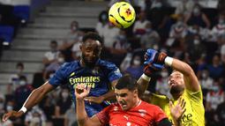 Penyerang Lyon, Moussa Dembele, berusaha menyundul bola saat menghadapi Nimes pada laga lanjutan Liga Prancis di Stadion Groupama, Sabtu (19/9/2020) dini hari WIB. Lyon bermain imbang 0-0 atas Nimes. (AFP/Jean-Philippe Ksiazek)