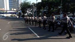 Sejumlah petugas kepolisian bersiap melakukan penjagaan di kawasan Bundaran HI, Jakarta, Senin (1/5). Seperti diketahui, puluhan ribu buruh akan berkumpul ke Ibu Kota untuk mengelar unjuk rasa peringatan Hari Buruh Internasional (Liputan6.com/Johan Tallo)