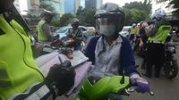 Polantas membuat surat tilang untuk pengendara motor ketika berlangsungnya Operasi Patuh Jaya 2018 di ruas Jalan DI Panjaitan, Jakarta Timur, Jumat (27/4). Razia ini berlangsung selama 14 hari, dari 26 April sampai 5 Mei 2018. (Merdeka.com/Imam Buhori)