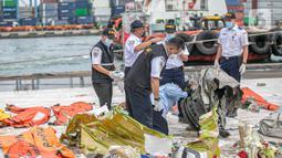 Petugas KNKT memeriksa bagian turbin pesawat Sriwijaya Air dihari kelima yang jatuh di perairan Pulau Seribu, di Dermaga JICT, Jakarta,  Rabu (13/1/2021). Pesawat Sriwijaya Air SJ 182 rute Jakarta-Pontianak  jatuh di perairan Kepulauan Seribu Sabtu (9/1) petang. (Liputan6.com/Faizal Fanani)