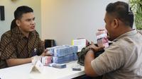 Petugas melayani penyetoran uang di cabang Bank Mandiri Pertamina UPMS III, Jakarta, Rabu (28/6). Bank Mandiri mengoperasikan 319 kantor cabang se-Indonesia secara bergantian pada musim liburan Idul Fitri 26-30 Juni 2017. (Liputan6.com/Angga Yuniar)