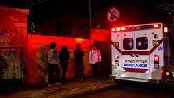 Warga setempat berdiri diseberang garasi parkir bawah tanah yang runtuh di sebuah kompleks di Mexico City (10/4). (AP Photo/Rebecca Blackwell)