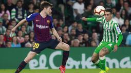 Pemain Real Betis, Tello Herrera, berebut bola dengan gelandang Barcelona, Sergi Roberto, pada laga La Liga 2019 di Stadion Benito Villamarin, Minggu (17/3). Barcelona menang 4-1 atas Real Betis. (AP/Miguel Morenatti)