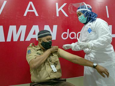 Vaksinator menyuntikkan vaksin COVID-19 kepada guru di SMA 70, Jakarta, Rabu (25/2/2021). Sebanyak 600 orang dari profesi guru, tenaga kependidikan, dan dosen akan divaksin COVID-19 hari ini. (Liputan6.com/Faizal Fanani)