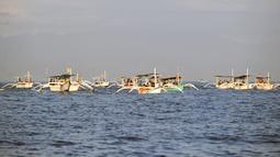 Wisatawan di atas perahu selama tamasya menyaksikan lumba-lumba di perairan Pantai Lovina di Singaraja, Bali, Jumat (30/10/2020). Pantai Lovina merupakan salah satu destinasi pariwisata di Bali yang sering dikunjungi untuk menikmati matahari terbit dan lumba-lumba di laut lepas (SONNY TUMBELAKA/AFP)
