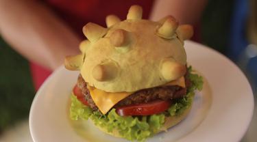 Pemilik restoran Hoang Tung menunjukkan burger berbentuk virus corona COVID-19 di Hanoi, Vietnam, Rabu (25/3/2020). Sebuah restoran di Hanoi membuat kreasi baru mereka yang disebut 'Burger Corona'. (AP Photo/Hau Dinh)