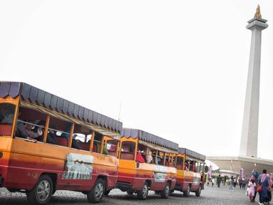 Kereta wisata membawa pengunjung mengelilingi kawasan Monumen Nasional (Monas), Jakarta, Sabtu (22/12). Libur sekolah yang berbarengan dengan libur Natal dan Tahun Baru dimanfaatkan masyarakat untuk pergi berwisata ke Monas. (Liputan6.com/Faizal Fanani)