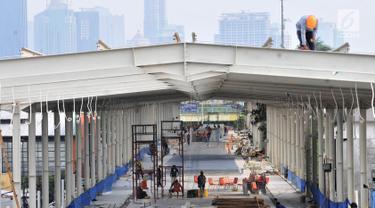 Aktivitas pekerja saat menyelesaikan pembangunan Skybridge Tanah Abang, Jakarta, Minggu (14/10). Jembatan yang menghubungkan Stasiun Tanah Abang dengan Pasar Blok G tersebut rencananya akan diresmikan pada 15 Oktober 2018. (Merdeka.com/Iqbal Nugroho)