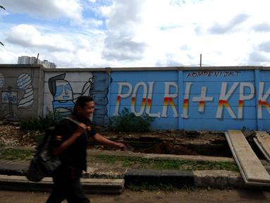 Seorang laki-laki melintas di depan mural di sisi Jalan Juanda, Depok, Jawa Barat. Foto diambil pada Senin (2/3/2015). (Liputan6.com/Helmi Fithriansyah)
