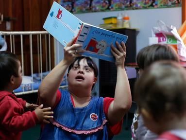 Seorang guru TK, Noelia Garella membacakan buku ke anak-anak saat bertugas di TK Jeromito, Cordoba, Argentina (24/10). Noelia 31 tahun merupakan penderita down syndrome pertama yang menjadi guru TK. (AFP Photo/Diego Lima)