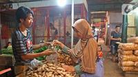 Pedagang melayani pembeli jahe di Pasar Induk Kramat Jati, Jakarta, Kamis (5/3/2020). Harga jahe mengalami kenaikan dari Rp25 ribu perkilogram kini dibanderol Rp35 ribu karena dipercaya mampu menangkal penyebaran virus corona Covid-19 yang sudah masuk Indonesia. (Liputan6.com/Herman Zakharia)