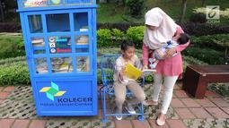 Seorang ibu menemani anaknya membaca buku yang tersedia di layanan Kotak Literasi Cerdas (Kolecer) di Taman Sempur, Bogor, Jawa Barat, Kamis (20/12). Kehadiran Kolecer bertujuan untuk menumbuhkan budaya literasi. (Merdeka.com/Arie Basuki)
