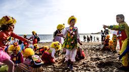 Anak-anak dengan pakaian badut bermain di pantai selama parade badut tahunan di Sesimbra, Portugal pada Senin (4/3/2019). Tidak hanya orang dewasa anak-anak pun ikut merias diri menjadi badut. (PATRICIA DE MELO MOREIRA / AFP)