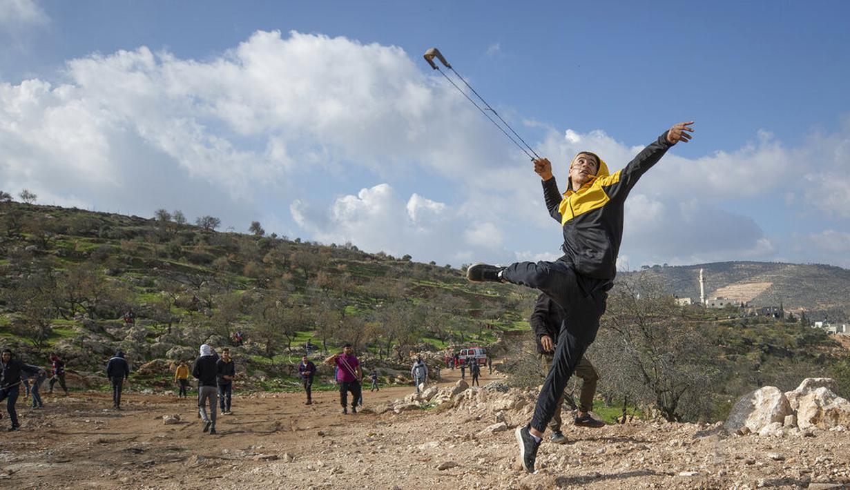 Pengunjuk rasa Palestina menggunakan ketapel saat bentrok melawan tentara Israel di Desa Mughayer, Ramallah, Tepi Barat, Jumat (18/12/2020). Pengunjuk rasa Palestina yang menggunakan ketapel terlibat bentrok dengan pemukim Yahudi yang menggunakan anjing. (AP Photo/Nasser Nasser)