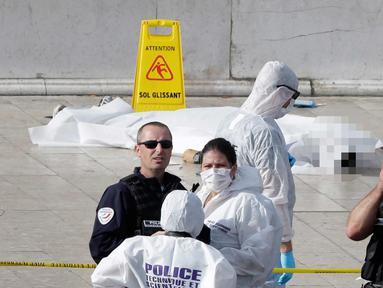Petugas berjaga di dekat korban penyerangan di luar stasiun kereta api Saint Charles, di Marseille, Prancis Selatan, (1/10). Dua orang tewas dalam sebuah serangan pisau yang dilakukan seorang pria di stasiun tersebut. (AP Photo/Claude Paris)