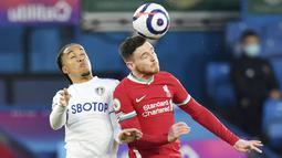Bek Liverpool, Andrew Robertson, duel udara dengan pemain Leeds United, Helder Costa, pada laga Liga Inggris di Stadion Elland Road, Senin (19/4/2021). Kedua tim bermain imbang 1-1. (Paul Ellis/Pool via AP)