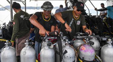 Penyelam memeriksa tangki oksigen saat bersiap melanjutkan pencarian korban kapal wisata yang terbalik di dermaga Chalong, Phuket, Sabtu (7/7). Kapal Phoenix yang membawa 105 penumpang tenggelam di Laut Andaman pada Kamis sore. (AFP/Mohd RASFAN)