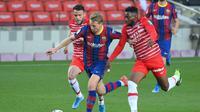 Pemain Barcelona, Frenkie De Jong, berusaha melewati adangan dua pemain Granada dalam laga jornada 33 La Liga di Camp Nou, Jumat (30/4/2021) dini hari WIB. Barcelona kalah 1-2 dari Granada dalam laga tersebut. (LLUIS GENE / AFP)