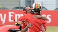 Pebalap Ferrari, Sebastian Vettel memeluk anggota timnya setelah finis di posisi terdepan dalam kualifikasi F1 GP di Sirkuit Hockenheim, Jerman, Sabtu (21/7). Vettel menorehkan waktu tercepat 1 menit 11,212 detik. (AP Photo/Jens Meyer)