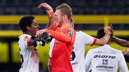 Pemain Mainz, Ridle Baku dan Florian Mueller, merayakan kemenangan atas Borussia Dortmund pada laga lanjutan Bundesliga di Signal Iduna Park, Dortmund, Kamis (18/6/2020) dini hari WIB. Borussia Dortmund menyerah 0-2 atas Mainz. (AFP/Guido Kirchner/pool)