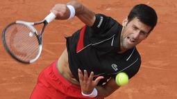 Petenis Serbia, Novak Djokovic mengembalikan bola ke petenis Italia Marco Cecchinato pada perempatfinal Prancis Terbuka 2018 di stadion Roland Garros, Selasa (5/6). Djokovic dikalahkan petenis non-unggulan dalam duel empat set. (AP/Alessandra Tarantino)
